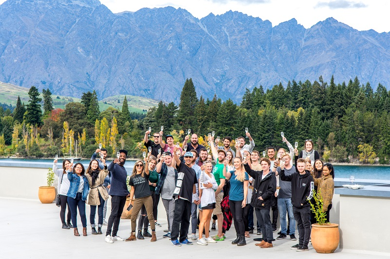 A group of hospitality workers raise wine glasses against the backdrop of Lake Wakatipu and The Remarkables