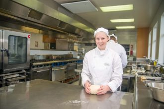 Sharnee Gardyne-Palmer stands in a commercial kitchen