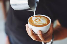 a barista pours milk into a cup of espresso coffee