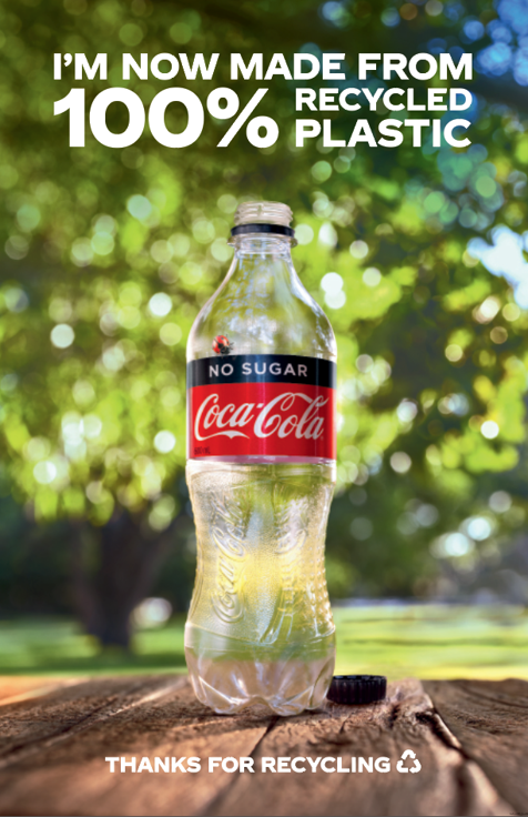"Empty coke bottle against nature background with ""I'M NOW MADE FROM 100% RECYCLED PLASTIC"" text"