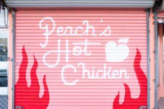 Peach's Hot Chicken text on pink garage door